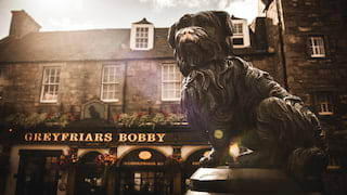 The Greyfriars Bobby bronze statue next to a pub of the same name in Edinburgh