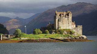 Medieval Scottish castle on an island in a loch surrounded by mountains