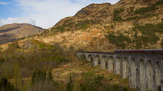 Burgundy train carriages on a stone arched viaduct over a grassy plain