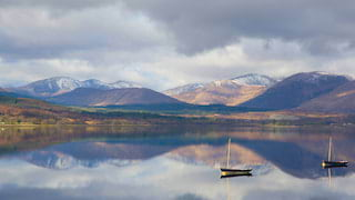 Small fishing boats floating on a mirror-still loch reflecting the snow-capped mountains