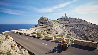 Person driving a vespa on a mountaintop road leading to a lighthouse in the distance