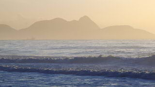Waves approaching Copacabana Beach at sunset with mountains beyond