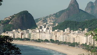 Copacabana beach lined with white high-rises and towering mountains beyond