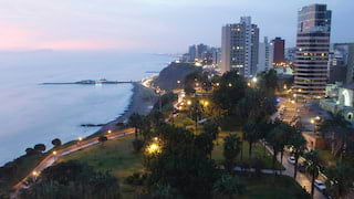 The shoreline of Lima at sunset with the twinkling cityscape beyond