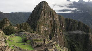 Aerial view of Machu Picchu citadel ruins under atmospheric clouds