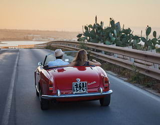 Couple in a red vintage car on driving along the Taormina coast