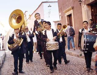 Banda di ottoni messicana sfila lungo una strada acciottolata