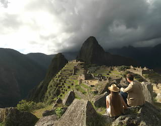 Casal sentado e admirando a cidadela de Machu Picchu