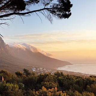 Table Mountain at sunrise of clouds over a mountain slope leading to the sea