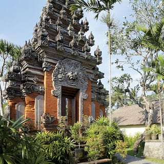 Ornate-tiered stone temple pagoda surrounded by shrubs and palm trees
