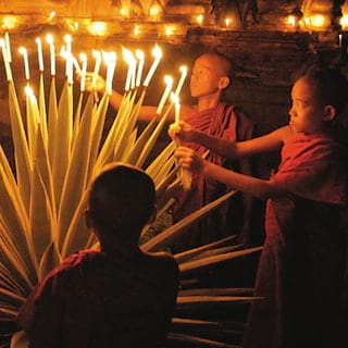 Red-robed buddhist monks lighting candles in a candlelit temple