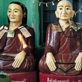 Carved wooden buddhist statues draped with fairy lights in a mint green room