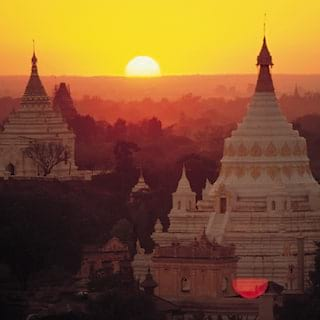Two ornate white stone pagodas with gold-tipped spires rising into a red sunset