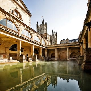 Open-air Roman bath surrounded by sandstone columns under blue skies