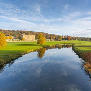 View of Chatsworth House from across manicured lawns and a river