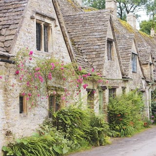 Row of idyllic stone cottages with tiled roofs in a medieval village square