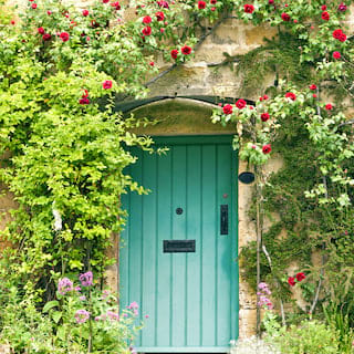 Idyllic sandstone cottage with a mint green wooden door surrounded by red flowers