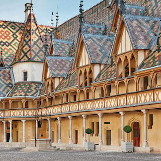 The distinctly patterned blue, green and red glazed roof tiles of the Beaune hospital
