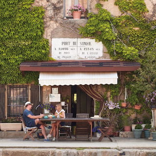 Smiling couple sitting at an outdoor table outside a rustic ivy-coated French cafe