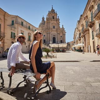 Couple sitting on a bench in an Italian piazza under clear blue skies