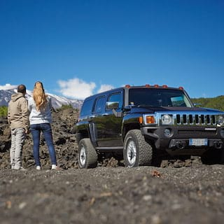 Two guests standing beside a range rover on the slopes of Mount Etna