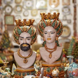 Two large ceramic busts in a shop brimming with ceramic ornaments