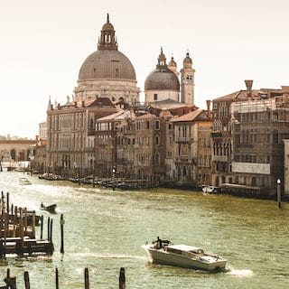 The Grand Canal in Venice alongside a domed cathedral and residences