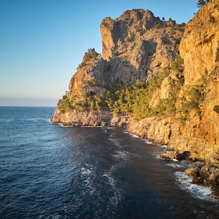 Craggy cliffside illuminated by sunset and curving into the ocean below