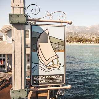 Sign reading 'Santa Barbara Stearns Wharf' hanging over emerald water