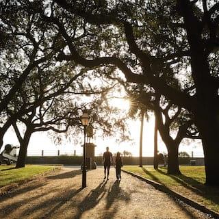 A couple walking through White Point Garden at sunset