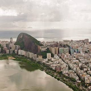Aerial view of Sugarloaf mountain rising above densely packed high-rises in Rio