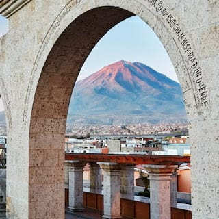 A row of stone arches inscribed with latin framing the mountain beyond at sunset