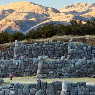 Rows of Inca stone walls with the Andean mountains in the background