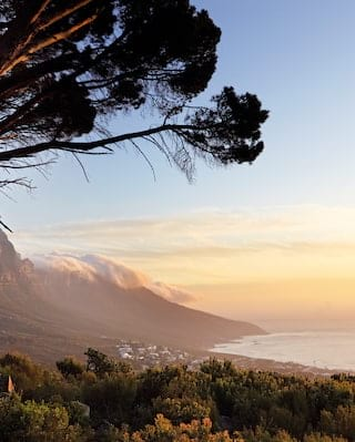 Table mountain range rolling down towards the sea at sunset