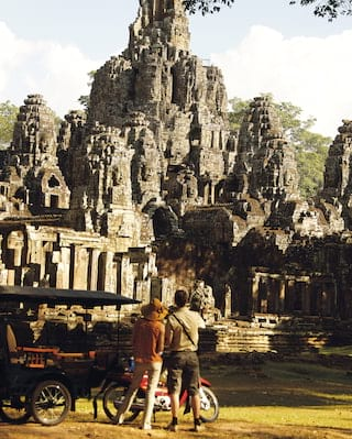 Two tourists standing on the grass in front of Angkor Thom Bayon temple to admire it