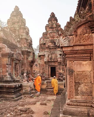 Two orange-robed monks among an ornate Khmer temple complex