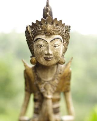 Close-up of a smiling traditional Balinese stone figurine