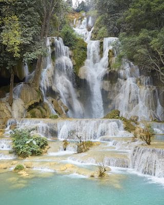 A collection of waterfalls spilling down a hillside, surrounded by jungle