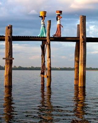 Two Burmese ladies carrying pots and walking along an ancient teak bridge