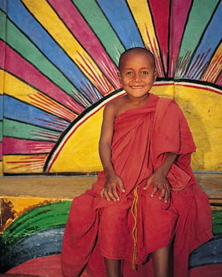 Smiling young buddhist monk kneeling in front of a sunburst wall mural