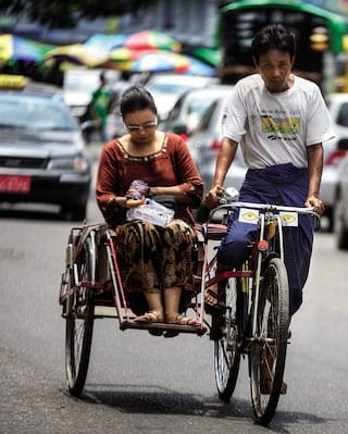 A lady being taxied on a rickshaw in front of Yangon traffic