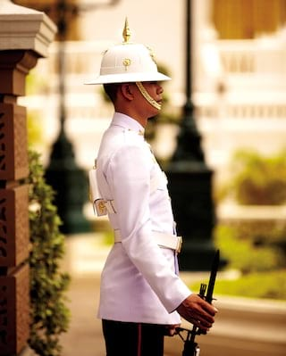 Guard in a white uniform with a helmet standing outside a temple