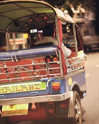 Close-up of a traditional Thai tuk-tuk motoring along a highway