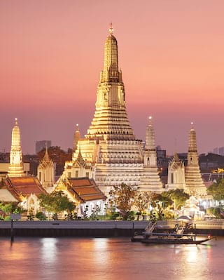 Ornate tiered temple pagoda rising above the Bangkok skyline in a pink sunset