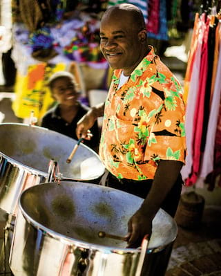 Man in a tropical shirt playing steel drums