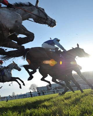 Close up of horses leaping over fences