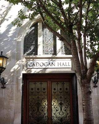 Exterior of Cadogan Hall with grand wooden double doors and stained glass windows