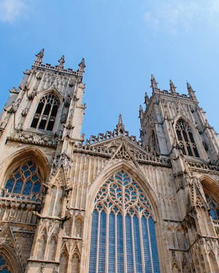 View from below of the ornate sandstone facade of York Minster under blue skies