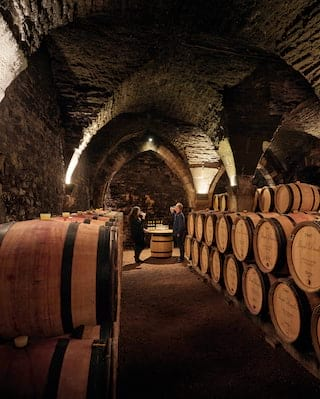 Double-height barrel-vaulted cellar lined with piles of wine barrels
