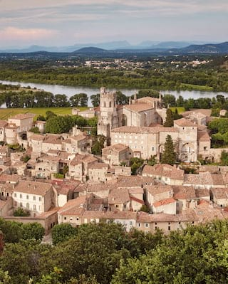 Aerial view of the terracotta roofs of Viviers, France, lush greenery surrounds with the river in the distance